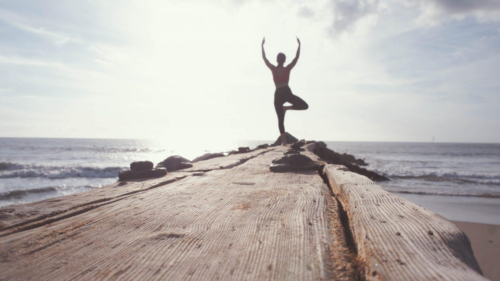 une silhouette se tient face à la mer en effectuant une position de yoga
