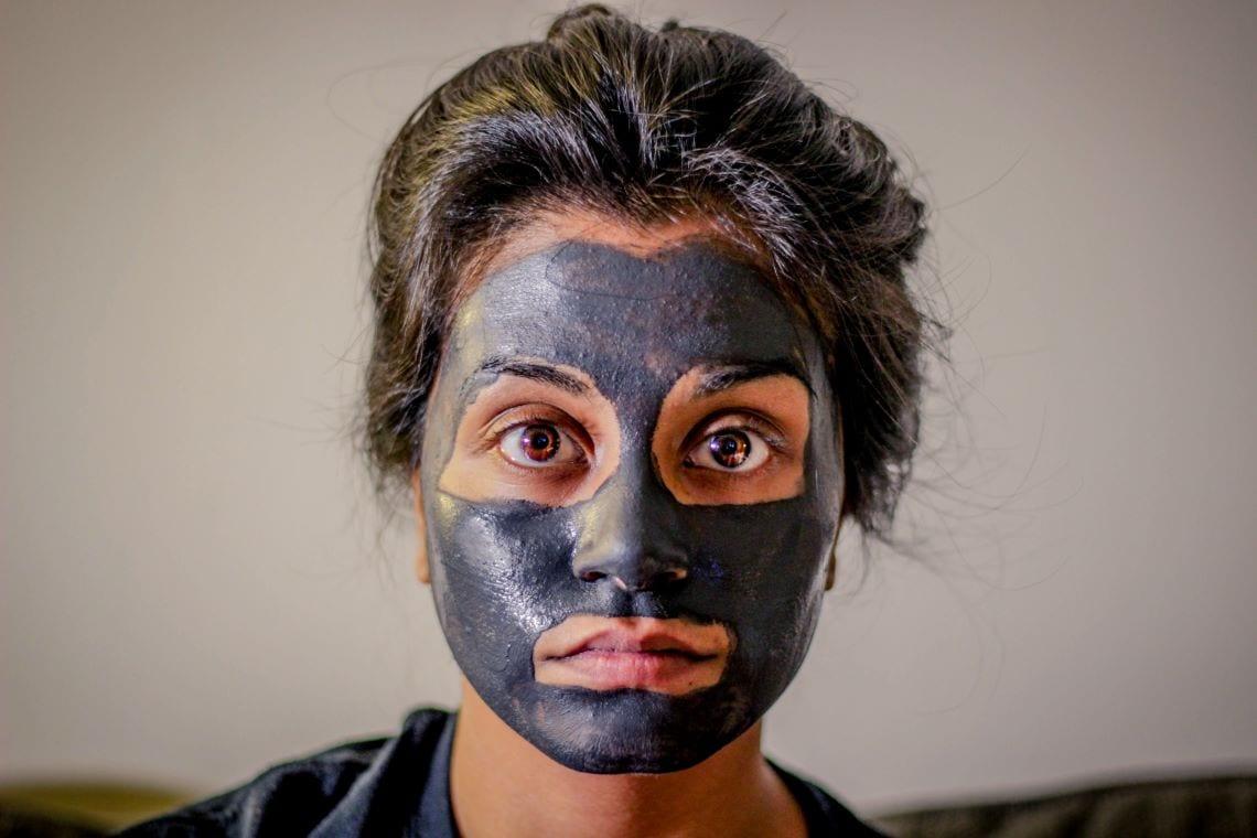 Jeune femme avec un masque de beauté sur le visage