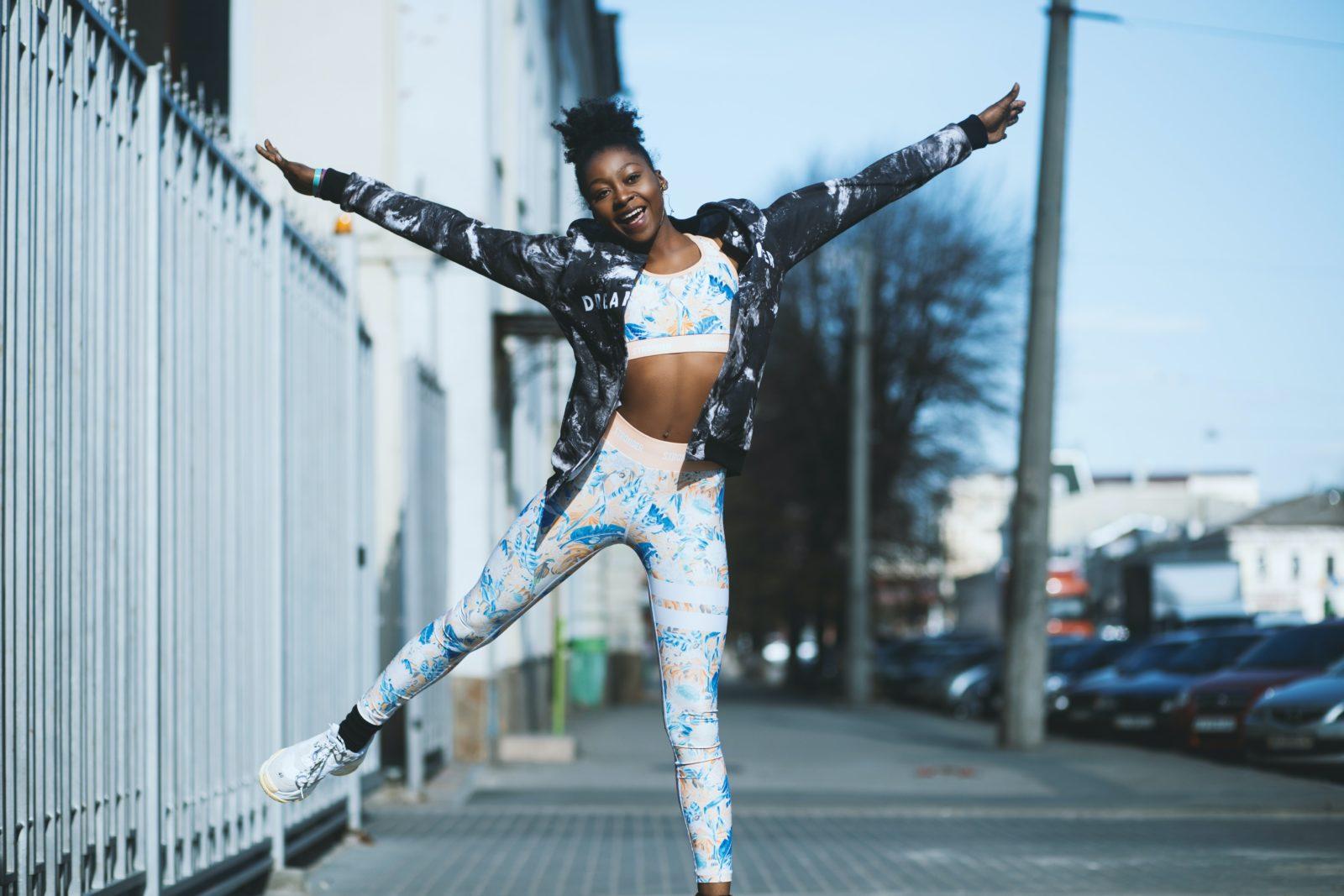 Femme portant le style vestimentaire répondant à la tendance Athleisure : legging et brassière de sport imprimés colorés, et sneakers.