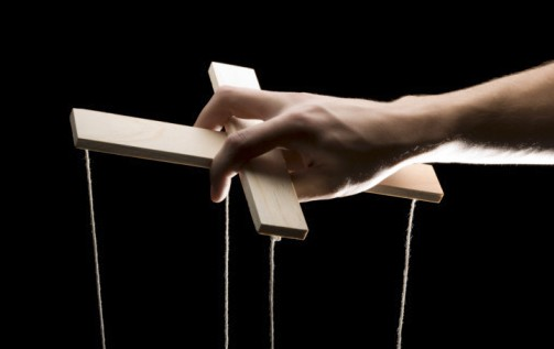 Main manipulant le support de bois servant à faire bouger une marionnette.