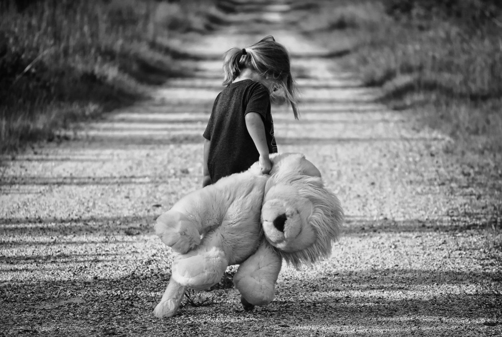 Petite fille marchant seule, tête baissée, en soulevant derrière elle un lion en peluche.