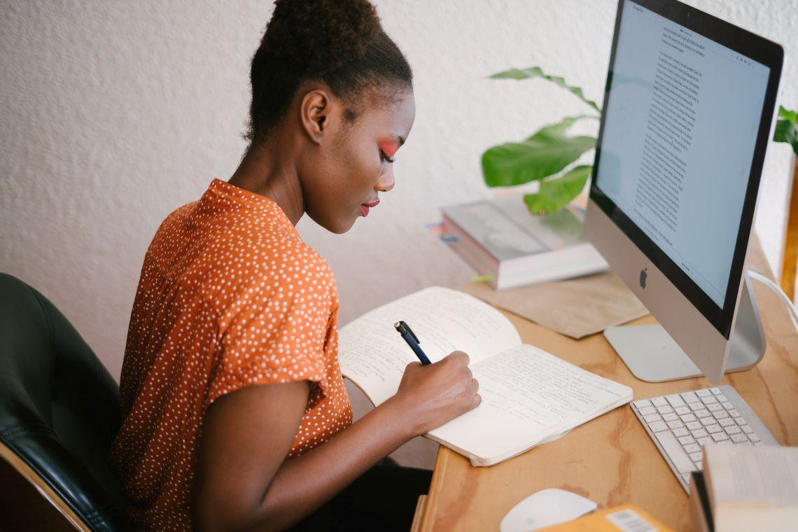 Une femme en train de prendre des notes sur un carnet. Source : Pexels.