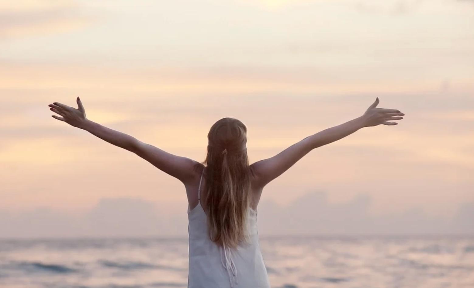 Femme libre qui étend ses bras sur une plage.