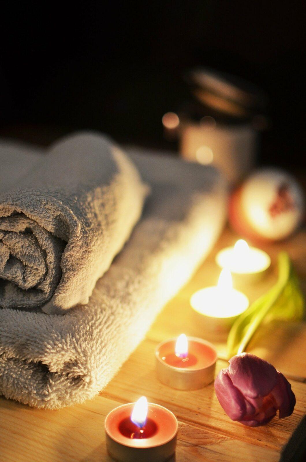 Ambiance de massage sensuel avec une rose et des bougies.