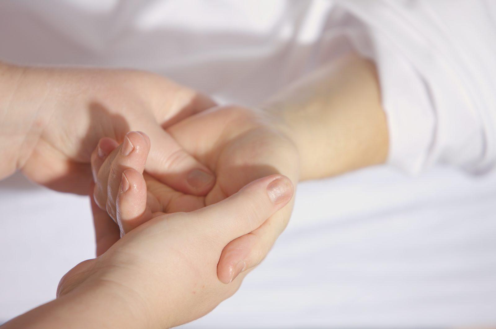 Massage énergétique Reiki réalisé sur une main pour détendre le corps et retrouver le bien-être. Le maître de Reiki exerce une pression avec son pouce dans la paume de la main du consultant.