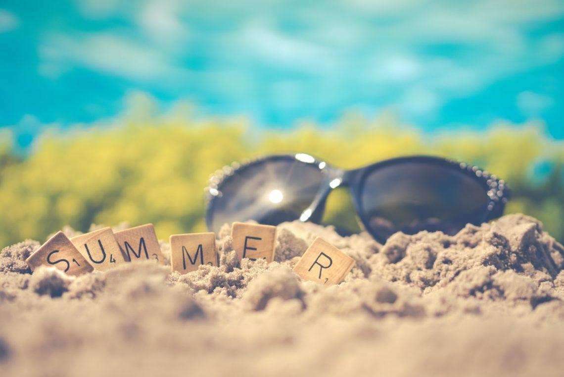 Lunettes de soleil et lettres formants le mot Summer dans le sable.